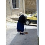 Woman sweeping the street. Photo by Alan Miller. All rights reserved.